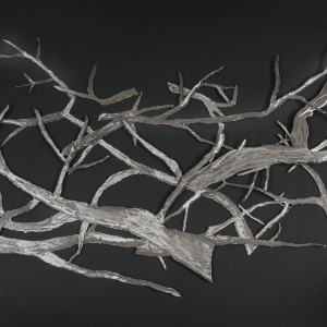 This is a wall mounted steel sculpture of multiple branch pieces.