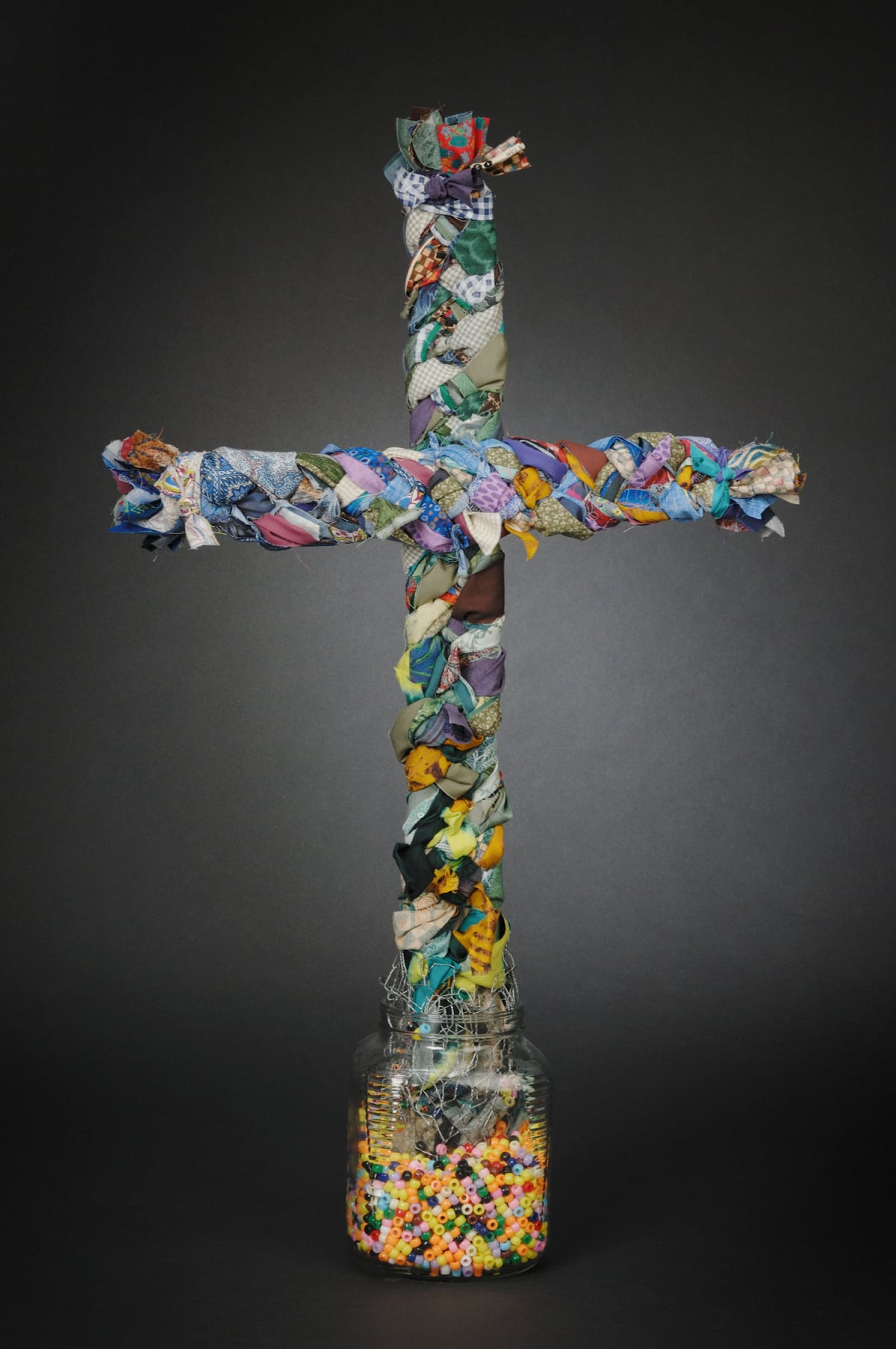 This is a 3-d cross made of fabric, wood, glass and beads.