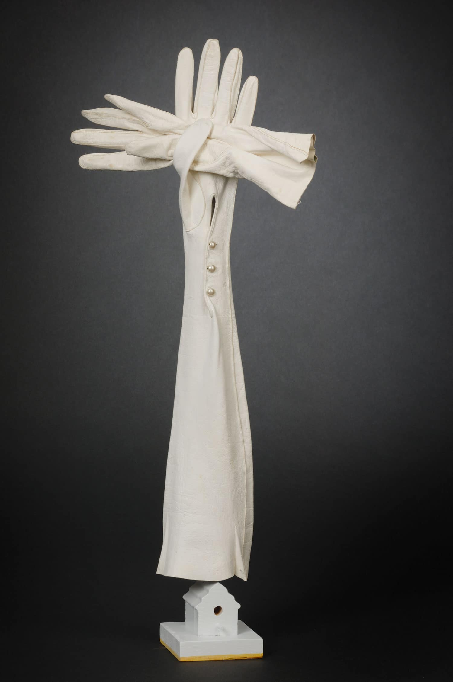 This is a 3-d cross made of White leather gloves, wood and wire and paint.