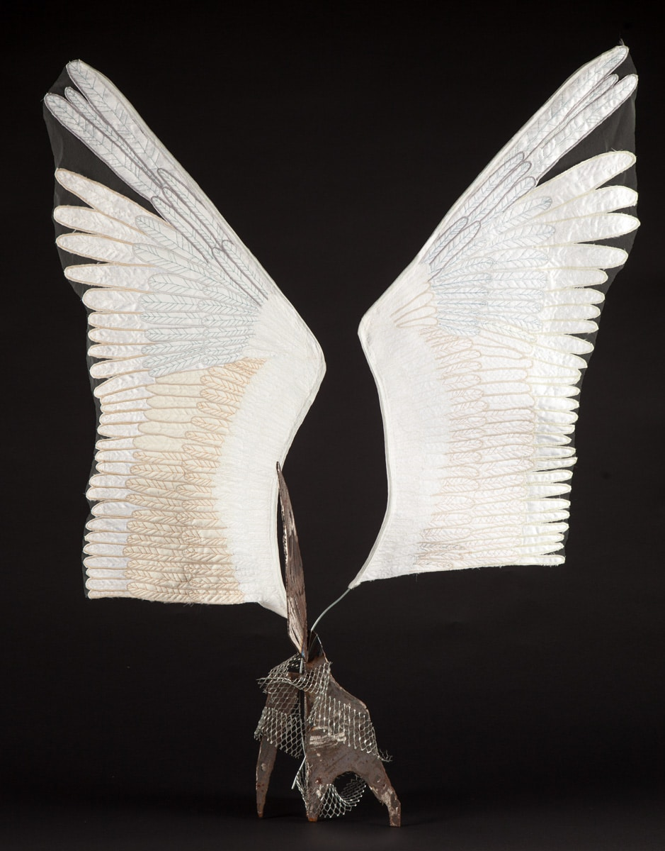 Welded steel base erupts into delicate looking fabric wings.